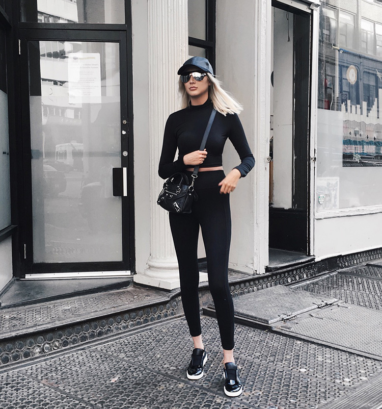 Carly Cristman wearing the athleisure trend in a black crop top with leggings