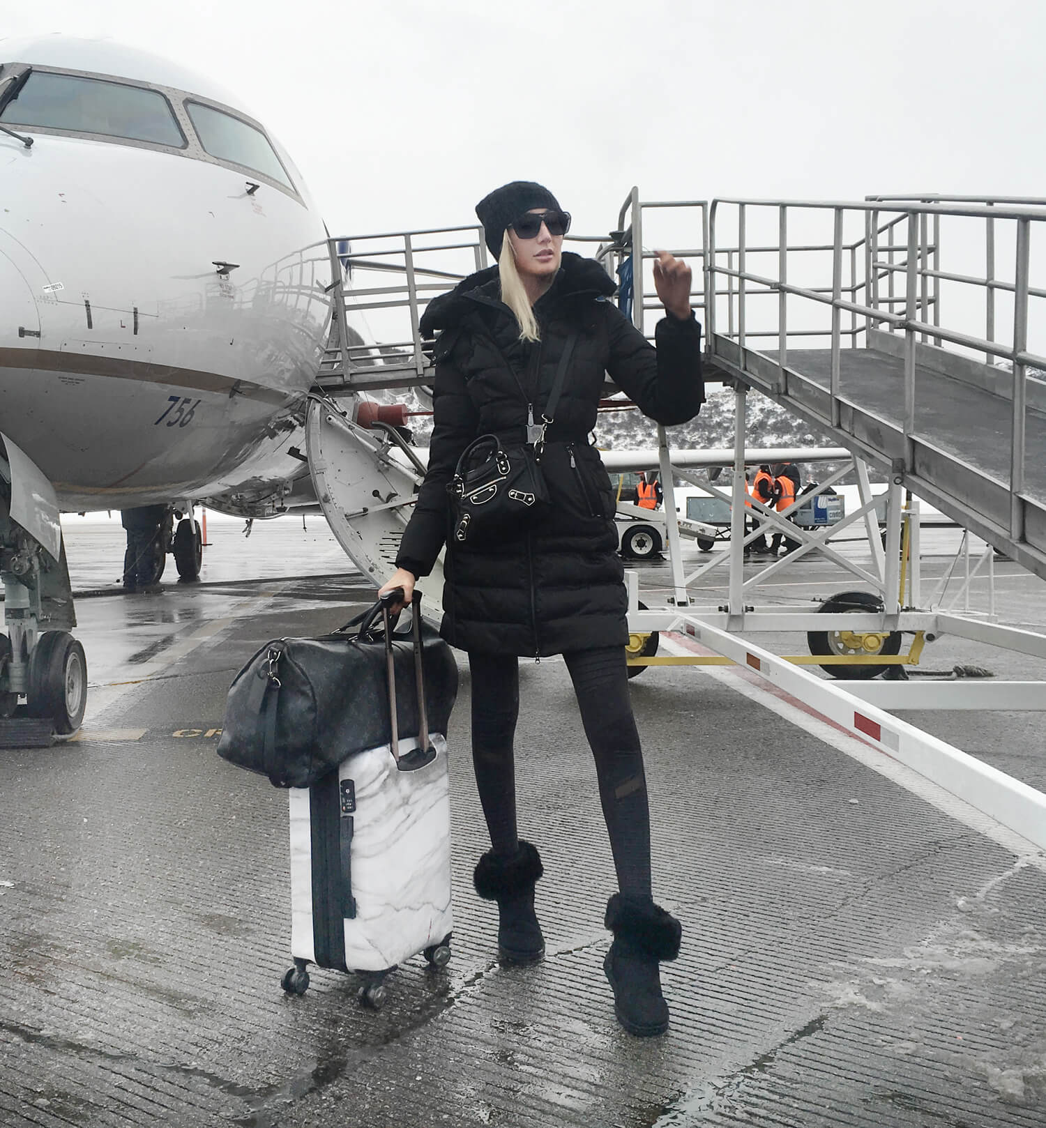 Airport Outfits, Cute Airport Outfits for Winter, Carly Cristman wearing Vince Camuto puffy jacket, Alo Moto Leggings, UGG boots, CalPak White Marble Suitcase