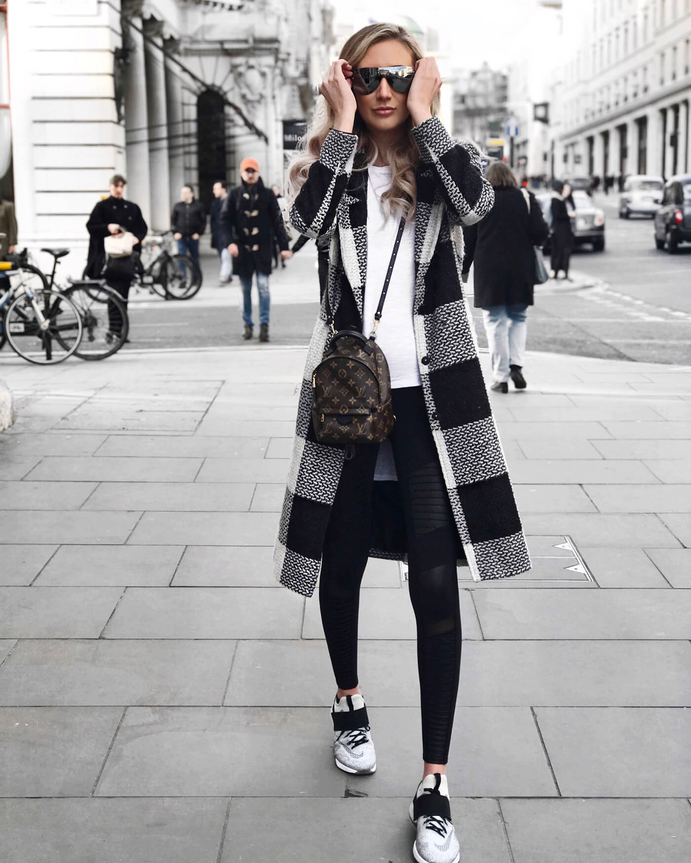Carly Cristman in London wearing a plaid coat with nike air zoom sneakers and moto leggings