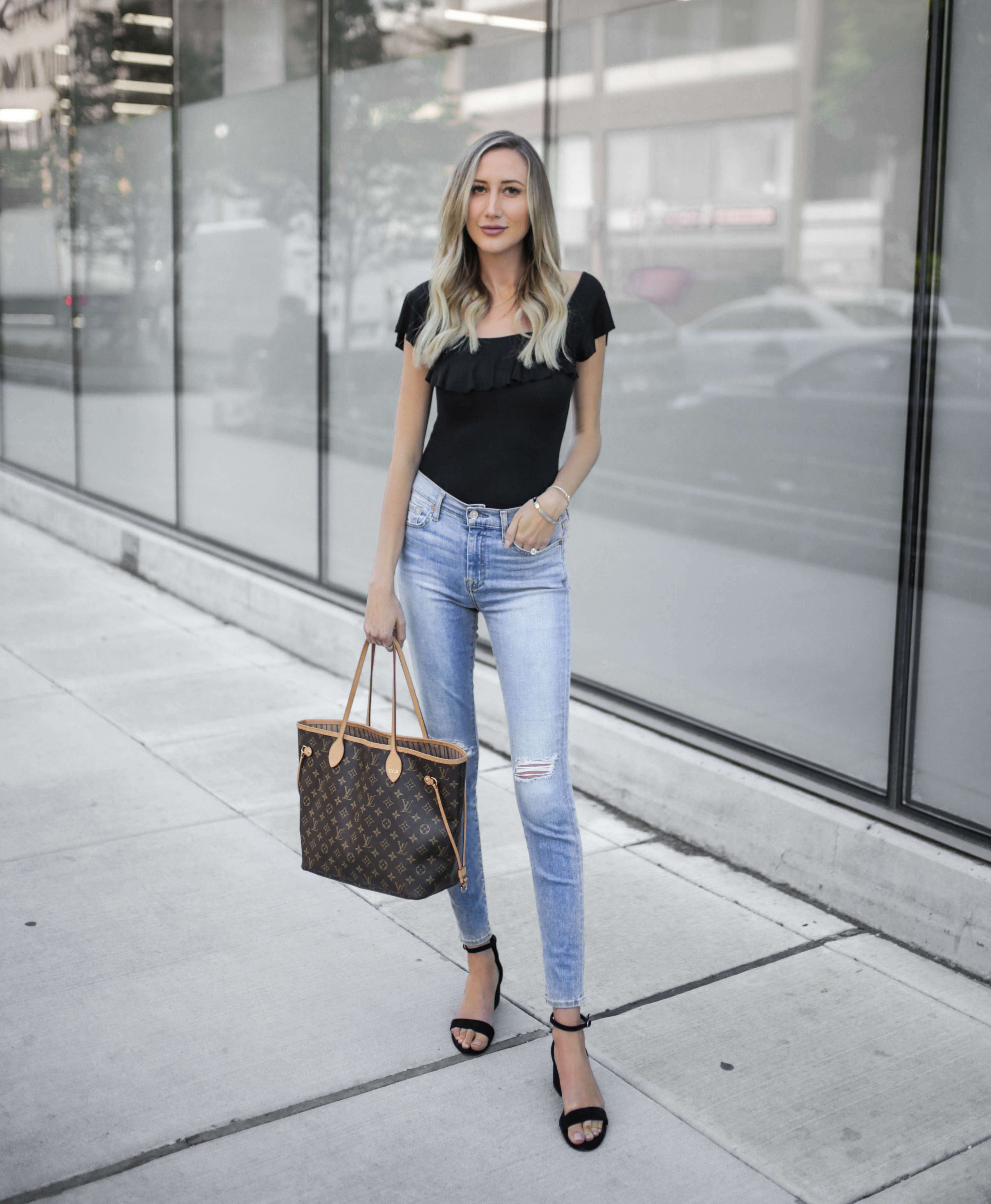Carly Cristman wearing a black ruffle top and 7 for All Mankind denim with Louis Vuitton Neverfull bag