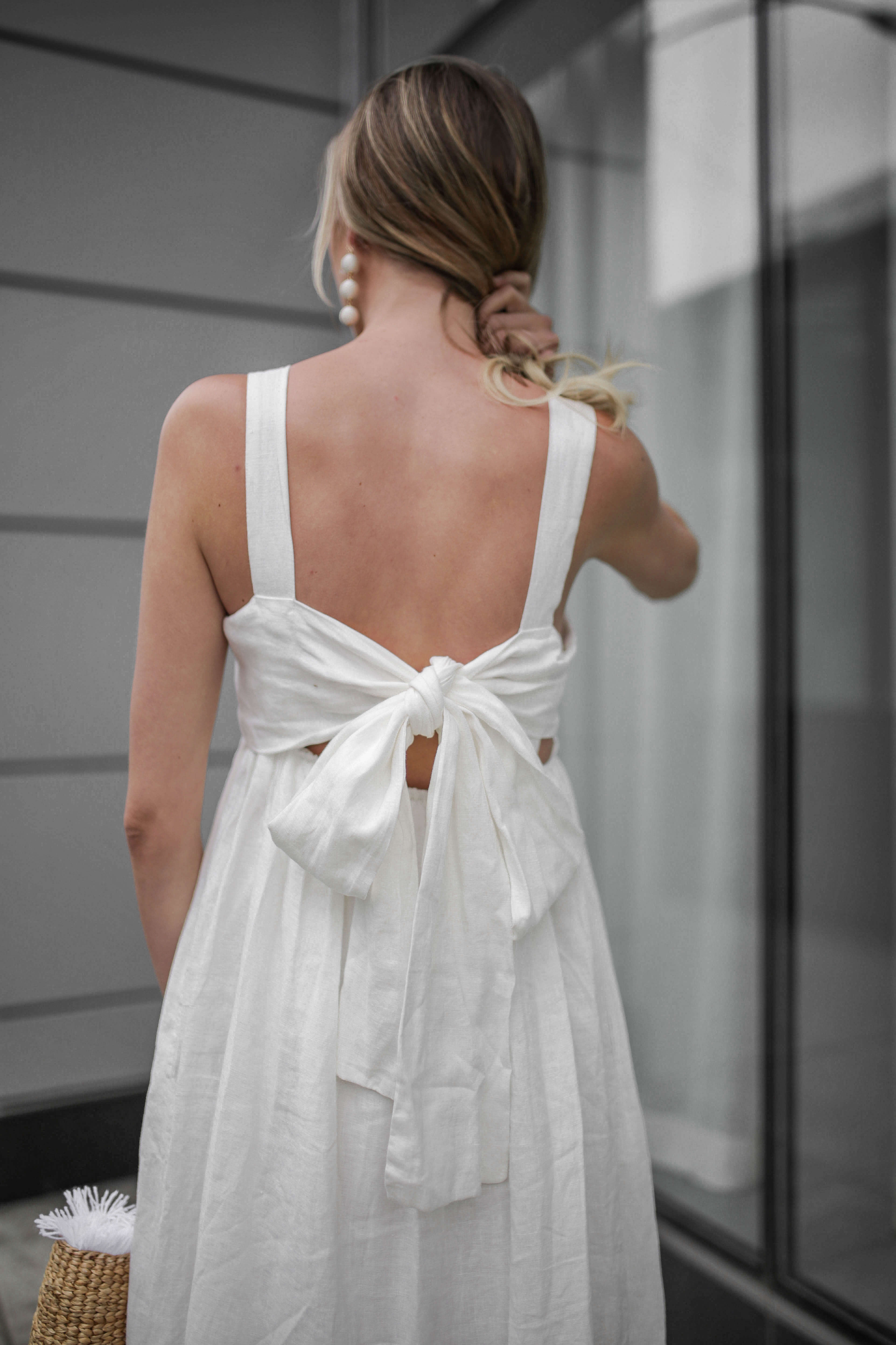 Carly Cristman wearing a summer white linen dress with bow back, Summer Trends 2018, CAARA Forget Me Not Linen Midi Dress, basket bag