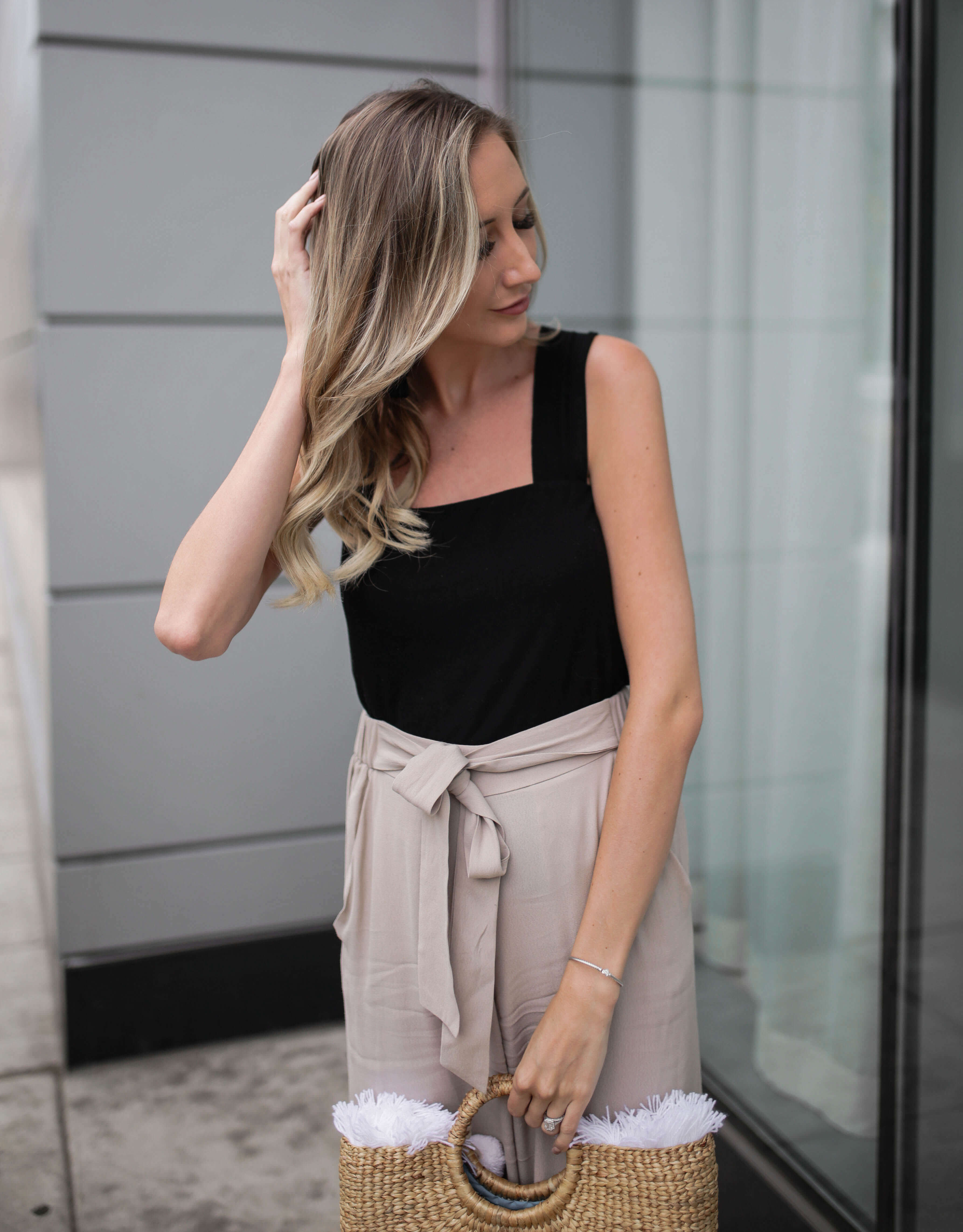 Carly Cristman wearing black tank top with taupe beige flowy cropped pants culottes. Summer outfit inspiration, basket bag, straw bags, easy summer outfits, neutral summer outfit, summer work attire