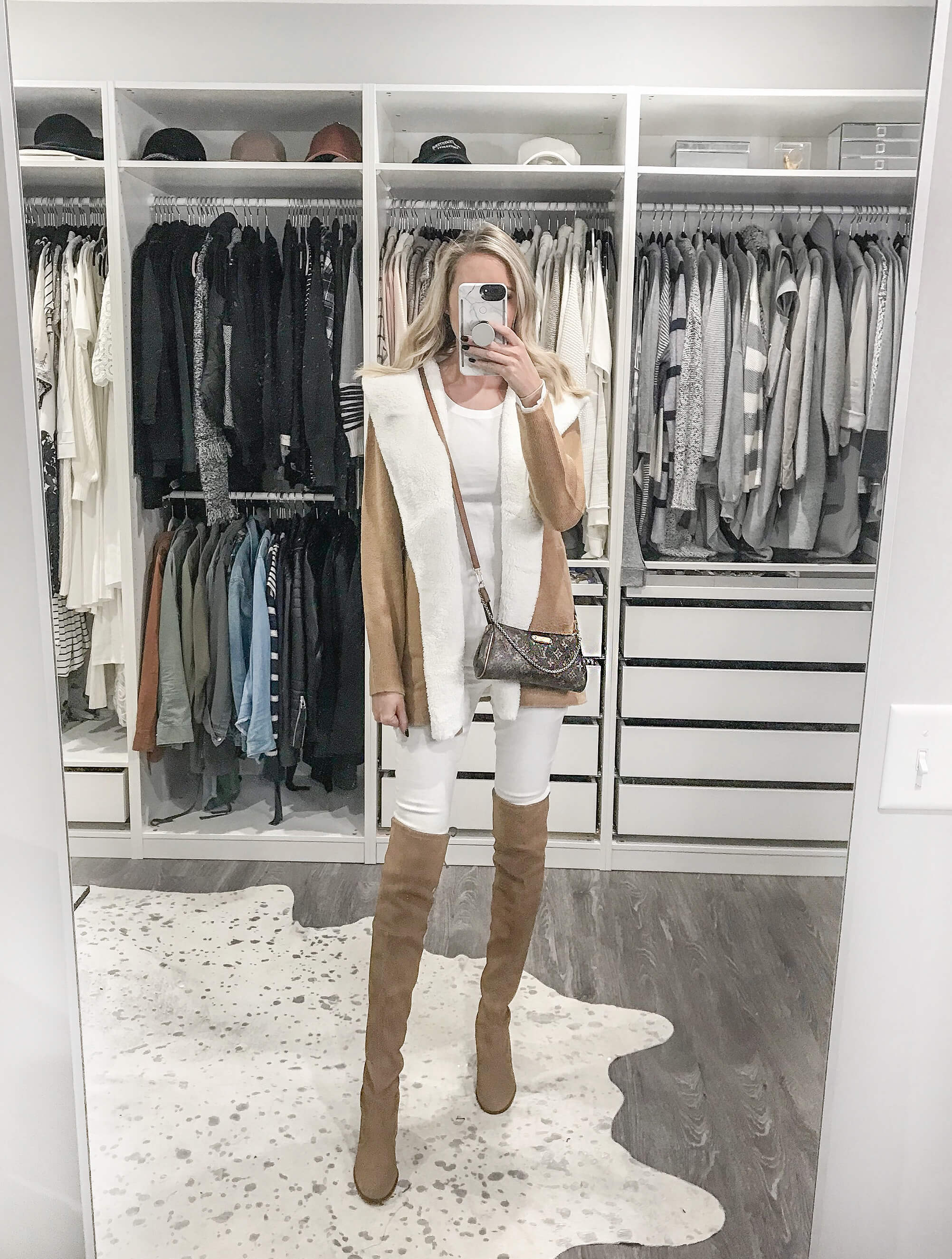 Carly Cristman wearing a faux shearling cardigan, white skinny jeans, tan over the knee boots